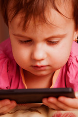 Social Media addiction. Little child girl typing text message on mobile phone (psychological problems, media mania, education concept)