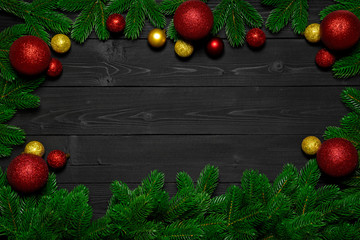 Christmas or New Year dark wood background. Xmas black board framed with season decorations, space for a text, view from above