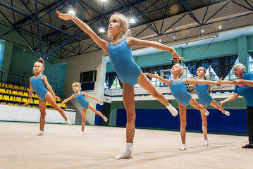 Foto op Plexiglas Gymnastiek little girls doing exercise in gym