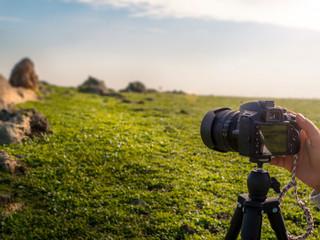 photographer taking landscape photo with dslr camera on tripod