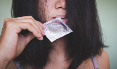 Sexy woman bite and hold condom, concept as love and protect AIDS