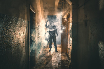 Silhouette of criminal or maniac with knife in hand in old scary corridor, man killer with cold weapon