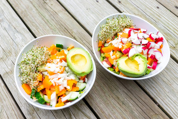 Two colorful big raw vegan salad bowls with alfalfa sprouts, avocado halves, chopped cucumber, orange bell pepper, red radish, lunch or dinner flat top view high angle wooden table