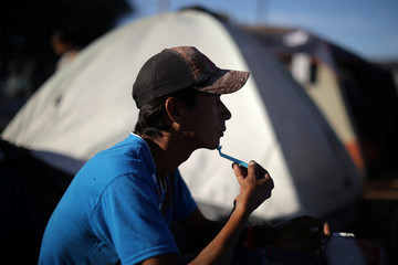 A migrant shaves and smokes in a temporary shelter in Tijuana