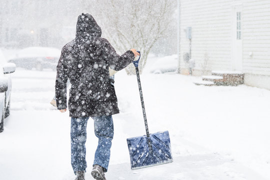 Back of young man, male walking in winter coat, cleaning, shoveling driveway from snow on street in heavy snowing snowstorm, holding shovel, residential houses