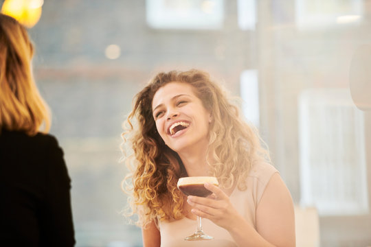 Laughing young woman holding espresso martini