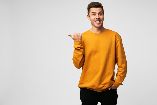 Young attractive handsome guy looks delighted gladden amazed, mouth open, smiling, like dream came true, big discount in shop,wears orange sweatshirt, points with thumb finger on a blank copyspace