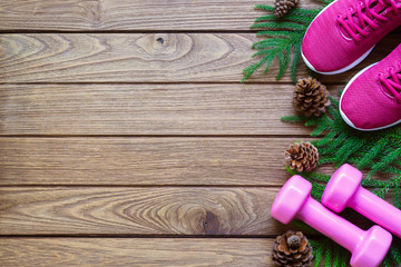 Fitness and Healthy Christmas sport composition. Flat lay of sport shoes, dumbbells pine leaves and pine cones. Merry Christmas and Happy new year concept special for fitness healthy lifestyle.