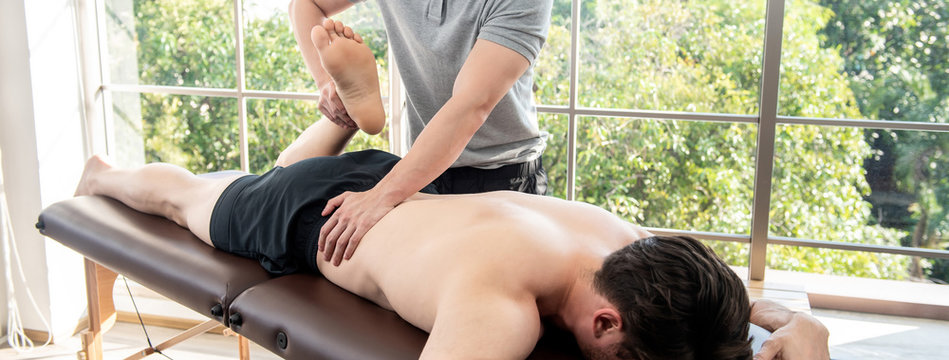Physiotherapist giving massage and stretching male patient in clinic
