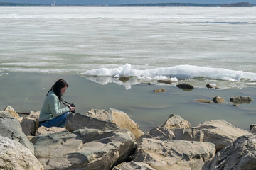 A girl in a warm jacket with a camera on the rocky shore of an ice-covered pond, taking pictures of the landscape