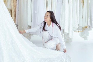 Asian woman making adjustment to bridal gown in wedding fashion store.