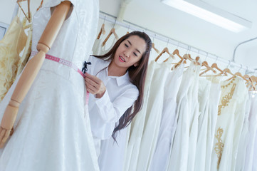 Professional wedding dress designer fitting bridal gown to woman in her store.