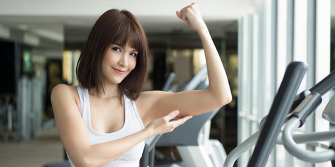 healthy strong fitness woman works out in gym. portrait of fitness woman in gym posing for strong body and arm, gym workout, weight training, healthy lifestyle concept. panorama banner crop format