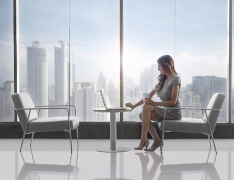 Traveling business woman working from laptop from high-rise building overlooking city skyline