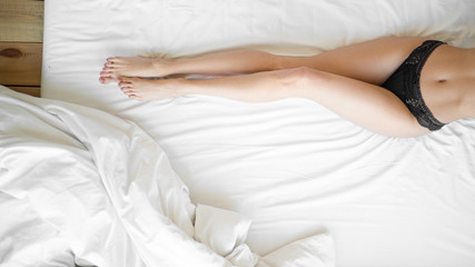 Poster Spa Gentle female legs on soft and comfortable bed linen