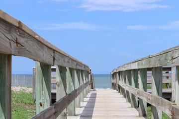 Perspective photograph of wood boardwalk railing beach access horizon blue sky, turquoise ocean and green grass.