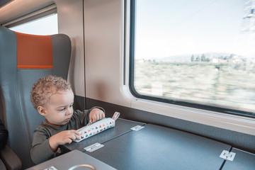 Cute little baby boy traveling by railway.