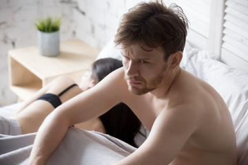 Young couple lying in bed under blanket in bedroom at home, woman in lingerie sleeping, sad, frustrated man thinking about relationships, family having sexual problems, impotence concept close up