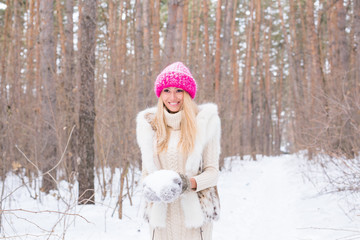 Fashion and people concept - Portrait of attractive young blonde woman dressed in white coat and pink hat in winter snowy park