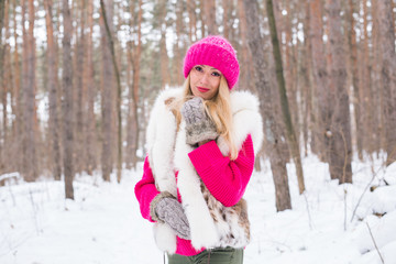 Beauty, nature and people concept - beautiful blond woman walking in pink hat and sweaters in winter wood and smiling