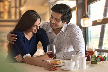 Happy young couple having food at restaurant table