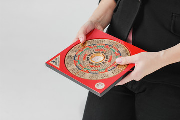 Chinese compass Lopan for Feng Shui technique in female hands isolated