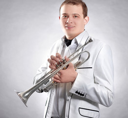 young man in a white suit with a trumpet.isolated on black background