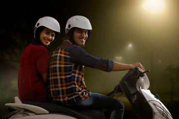 Cheerful young couple riding on a motorbike at night