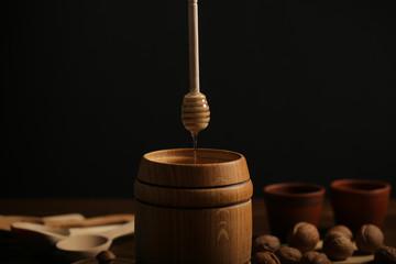 мёд в бочке свежий урожай и орехи разные стоят на столе