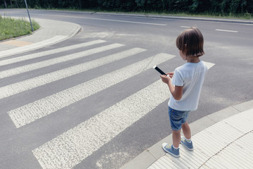 Boy with a smartphone standing at pedestrian crossing next to the road