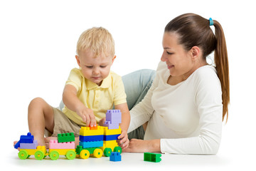 Mother and child build out of colorful plastic blocks. Family and childhood concept. Isolated on white background