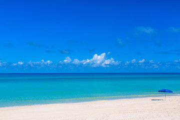 Blue beach umbrella parasol on the tropical beach. Vacation background. Idyllic beach landscape.