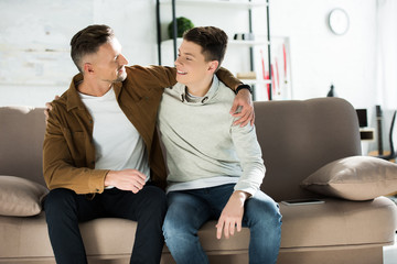 happy father and teen son hugging on sofa at home