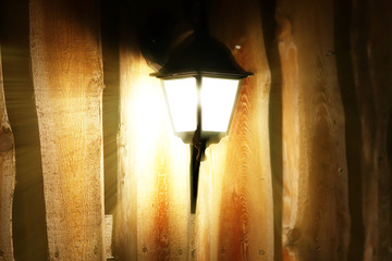 Glowing street lamp on the background of a wooden fence at night. Light permeates the darkness. Street lighting. Creating a cozy and romantic atmosphere. Elements of scenery and design.