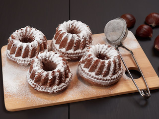Miniature Chestnut Bundt Cakes with Chocolate Chips on a bamboo cutting board, on a dark brown background