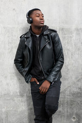 cool young black man in leather jacket listening to music with headphones