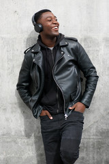 smiling black man in leather jacket listening to music with headphones