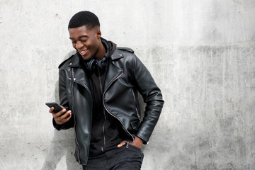happy black man in leather jacket looking at mobile phone