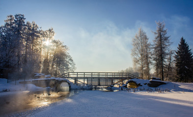 Winter landscape in clear weather. Morning bright sun. Snow plays shine. Frosty Snow Park