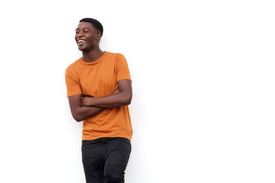 happy young black guy laughing with arms crossed against isolated white background