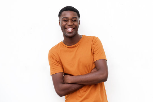 young happy black guy laughing with arms crossed against isolated white background