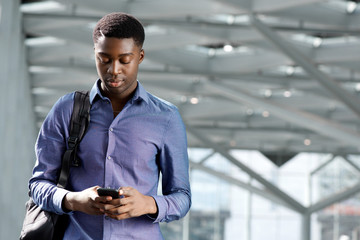 young african american businessman with bag looking at cellphone