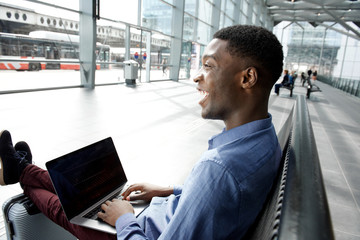 Side of african american businessman waiting at station with laptop