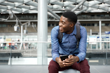 happy young travel man sitting on suitcase with mobile phone