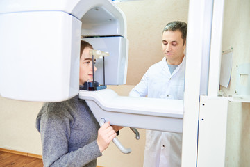 dental tomography. Girl-patient stands in a tomograph, a doctor near the control panel