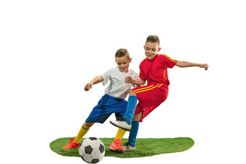 Young boys with soccer ball doing flying kick, isolated on white. football soccer players in motion on studio background. Fit jumping boys in action, jump, movement at game.