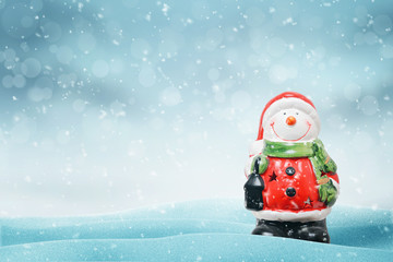 Cute snowman like Santa Claus on snow. Copy space on left side. Blue background with snowflakes and bokeh.