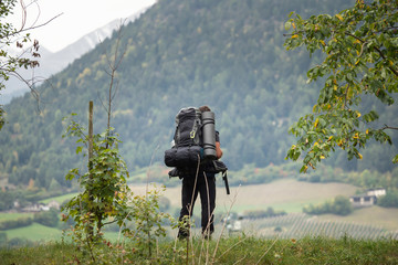 A hiker with a backpack looks into the distance