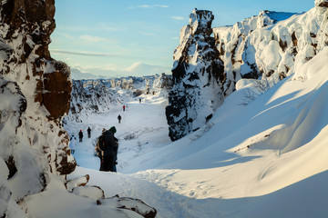 People walking through the continental divide, Thingvellir national park, Iceland. Bright and sunny day with cobalt blue sky