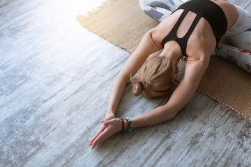 Top view of beautiful young fitness woman in sportswear working out on white wooden floor at home, doing yoga exercise, full length